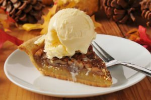 a slice of pecan pie with vanilla ice cream on a colorful holiday table